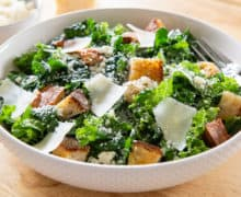 White Dotted Bowl Filled with Kale Greens Dressed in Caesar Dressing and Croutons