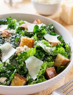Kale Caesar Salad - in White Textured Bowl With Homemade Scratch Dressing and Homemade Croutons