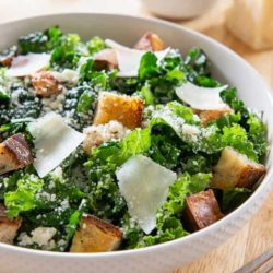 Kale Caesar Salad in White Bowl with Parmesan Shavings on Top