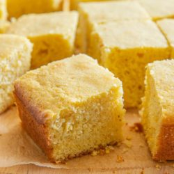 Closeup of a square of cornbread, with more pieces surrounding on parchment paper