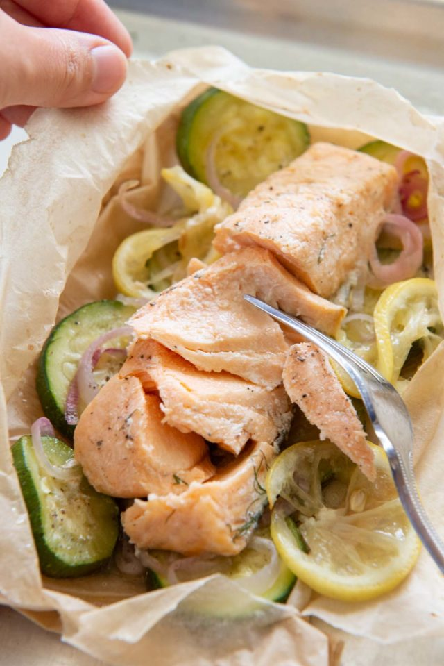 Salmon En Papillote - On Sheet Pan with Fork Breaking Up The Salmon Fillet
