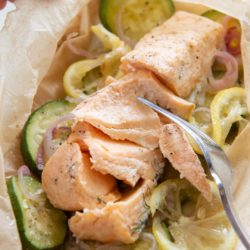 Salmon En Papillote with Zucchini and Lemon Slices with Fork Flaking the Fish