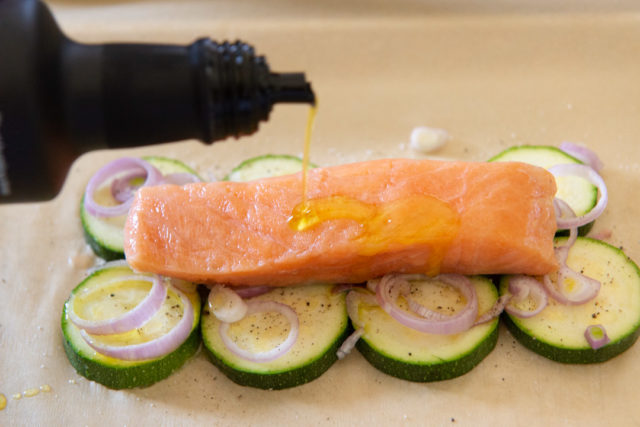 Drizzling Olive Oil On a Salmon Fillet Atop Zucchini Slices