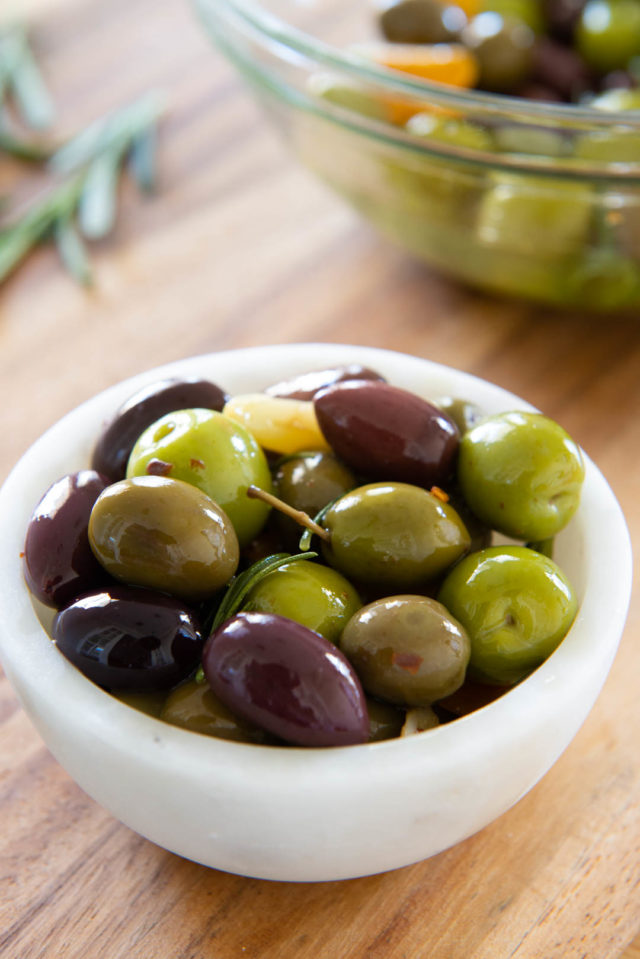 Marinated Olives - In a White Bowl on a Wooden Board
