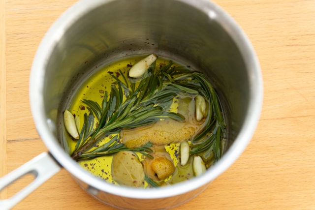 Warmed Olive Oil, Rosemary, Citrus Zest, and Garlic in Saucepan
