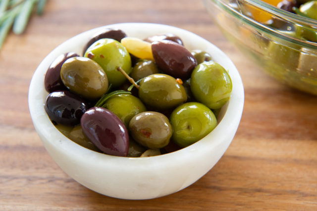 Greek Olive Mix Marinated and Served in White Bowl on Wooden Board