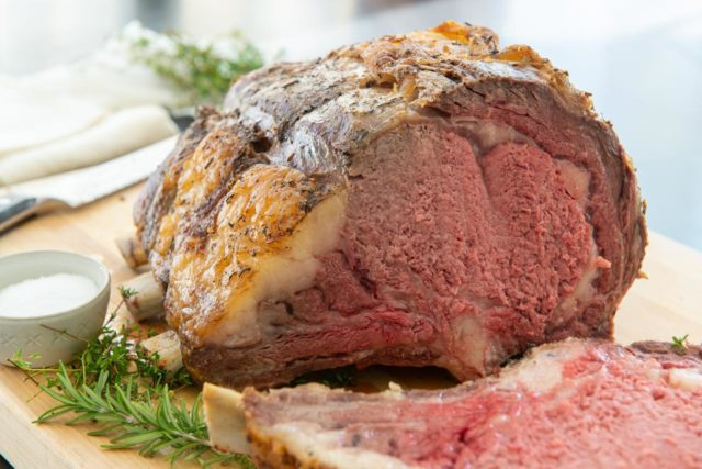 Prime Rib Roast - Standing on a Wooden Board with Slice Cut