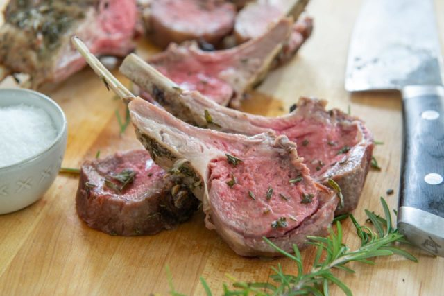 Rack of Lamb Chops on a Wooden Board with Rosemary and Salt