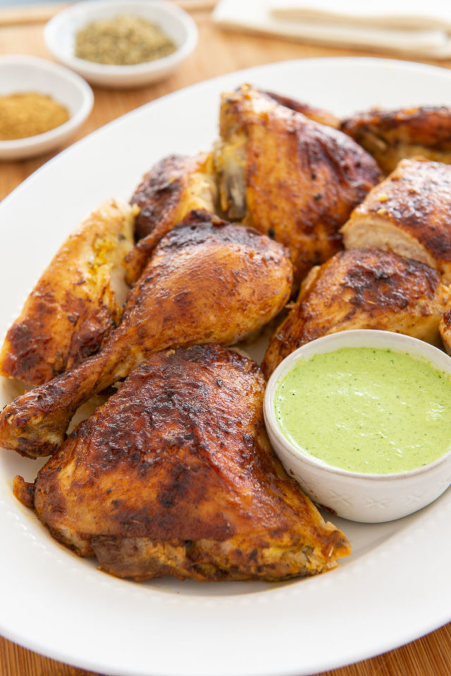 Peruvian Chicken - Cut Into Pieces on White Platter with Green Sauce