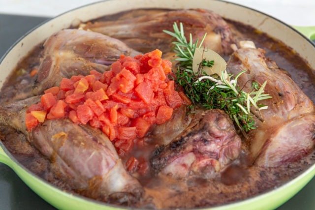Braising Liquid with Meat Back in Pan with Tomatoes and Fresh Rosemary