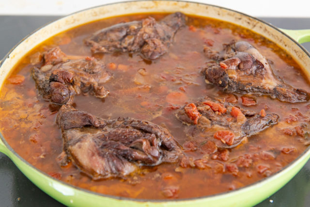 Lamb Shanks Cooking in Tomato Sauce in Green Braiser