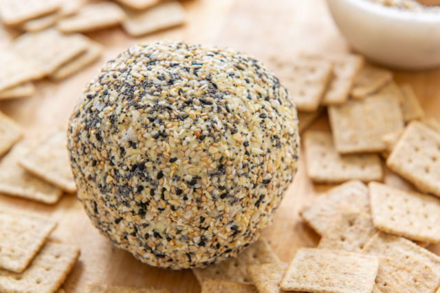 Everything Bagel Cheese Ball - With Crackers on Wooden Board