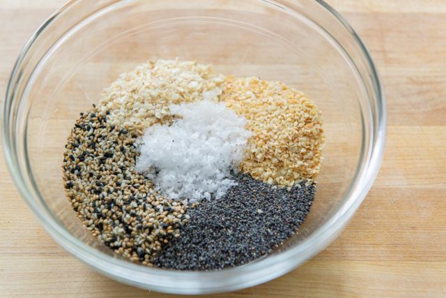 Glass Bowl with Sesame Seeds, Dried Garlic Flakes, Dried Onion Flakes, Poppy Seeds, and Maldon Sea Salt Flakes
