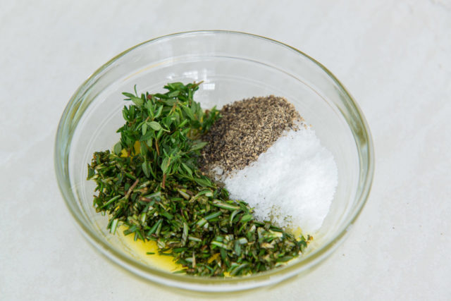 Herbs, ghee, salt, and pepper in a glass bowl