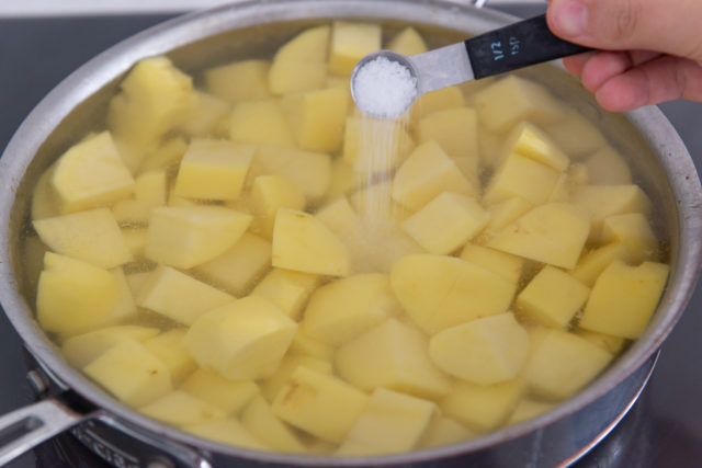 Chunks of Yukon Gold Potatoes in Water in Pan with Salt