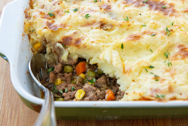 Easy Shepherd's Pie Recipe - Shown in Casserole Dish with Serving Spoon and Thyme on Top