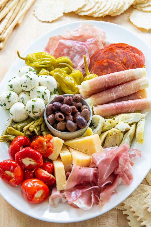 Antipasto - On a White Platter with Olives, Stuffed Peppers, Prosciutto, and Cheeses