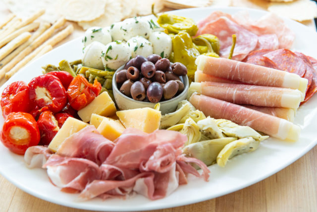 Antipasto Recipe - Arranged on a White Dish with Olives, Charcuterie, Cheese, and Peppers