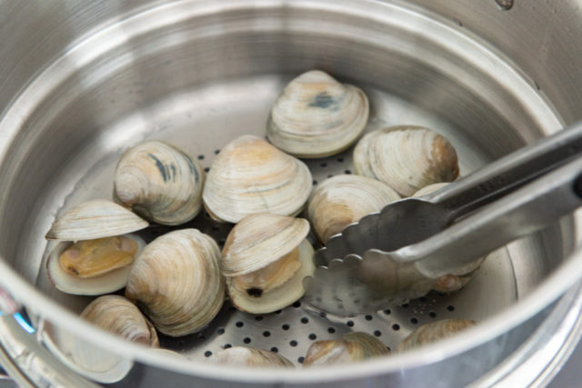 Partially opened steamed clams in a stainless steel pan with tongs