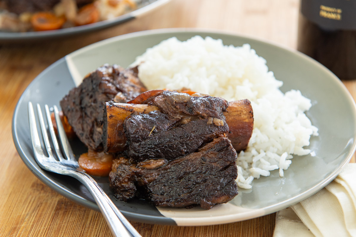 Slow Cooker Beef Short Ribs Plated with White Rice and a Fork with Wine in Back