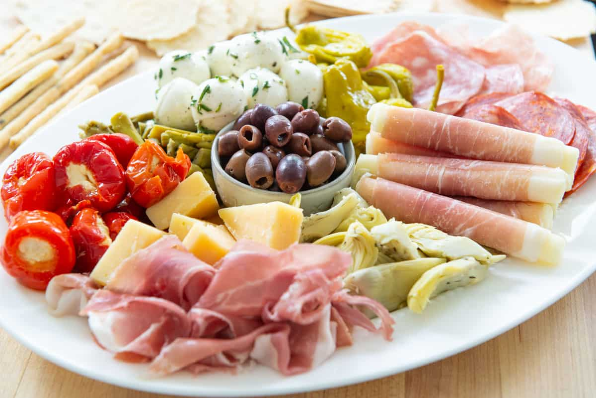 Antipasto Recipe Arranged on a White Dish with Olives, Charcuterie, Cheese, and Peppers