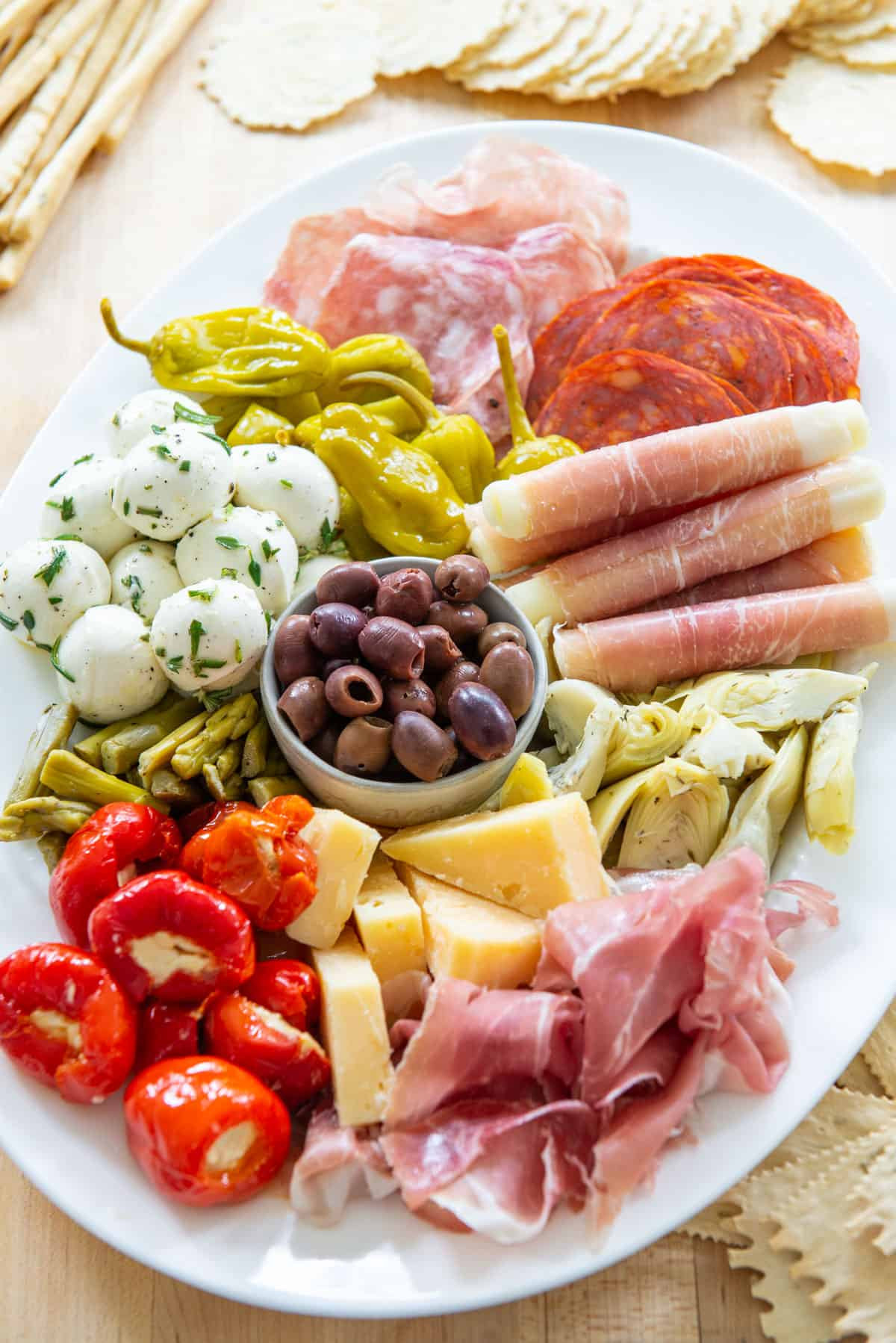 Antipasto On a White Platter with Olives, Stuffed Peppers, Prosciutto, and Cheeses