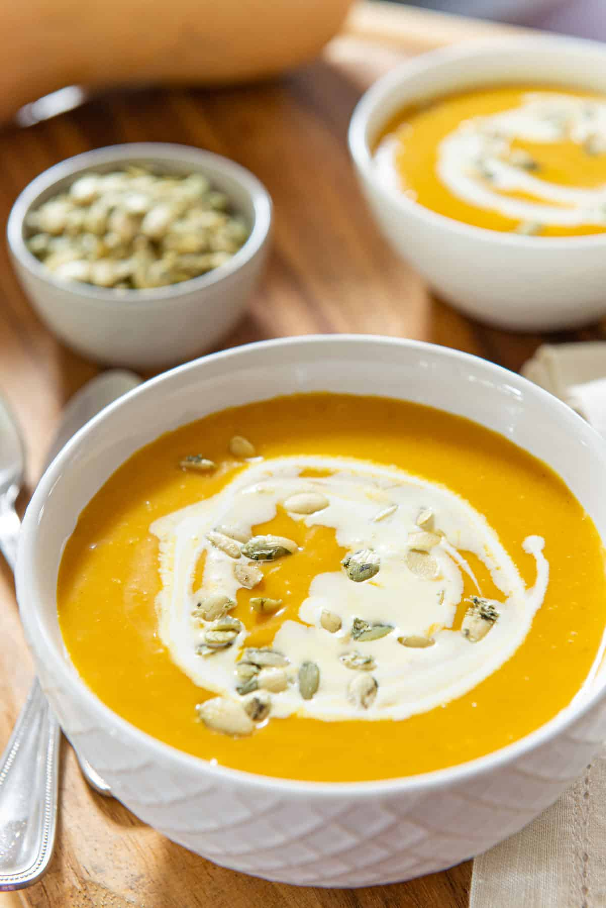 Butternut Squash Soup In White bowl with Cream and Pumpkin Seed Garnish