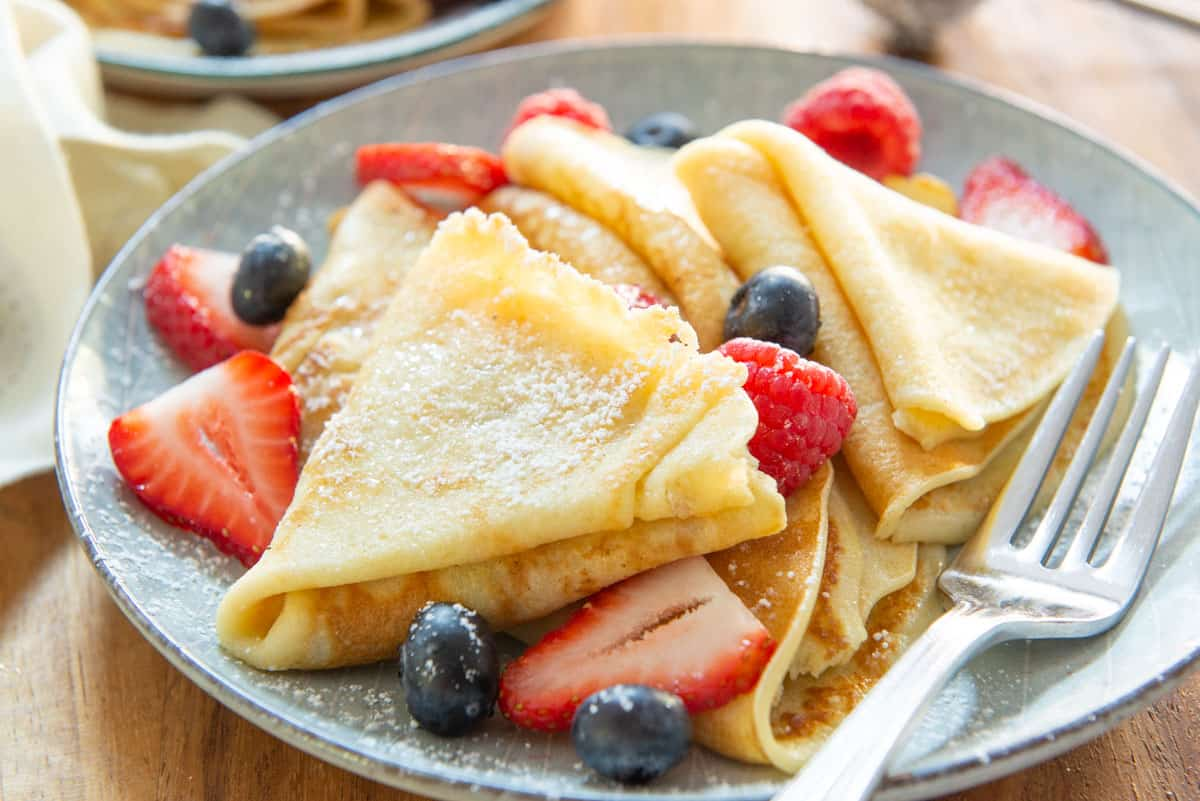 Crepes Recipe Presented On a Plate Dusted with Powdered Sugar and Served with Berries