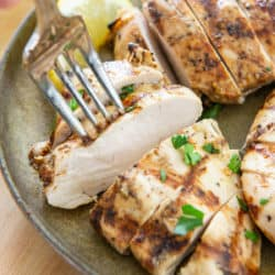 Grilled Chicken Breast Sliced On a Plate with Fork and Lemon
