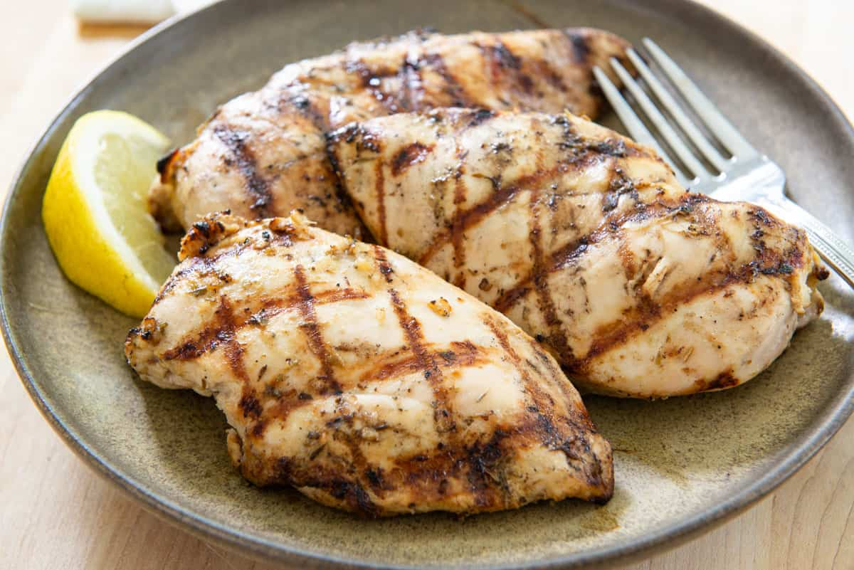 Three Grilled Chicken Breasts On a Plate with Lemon Wedge