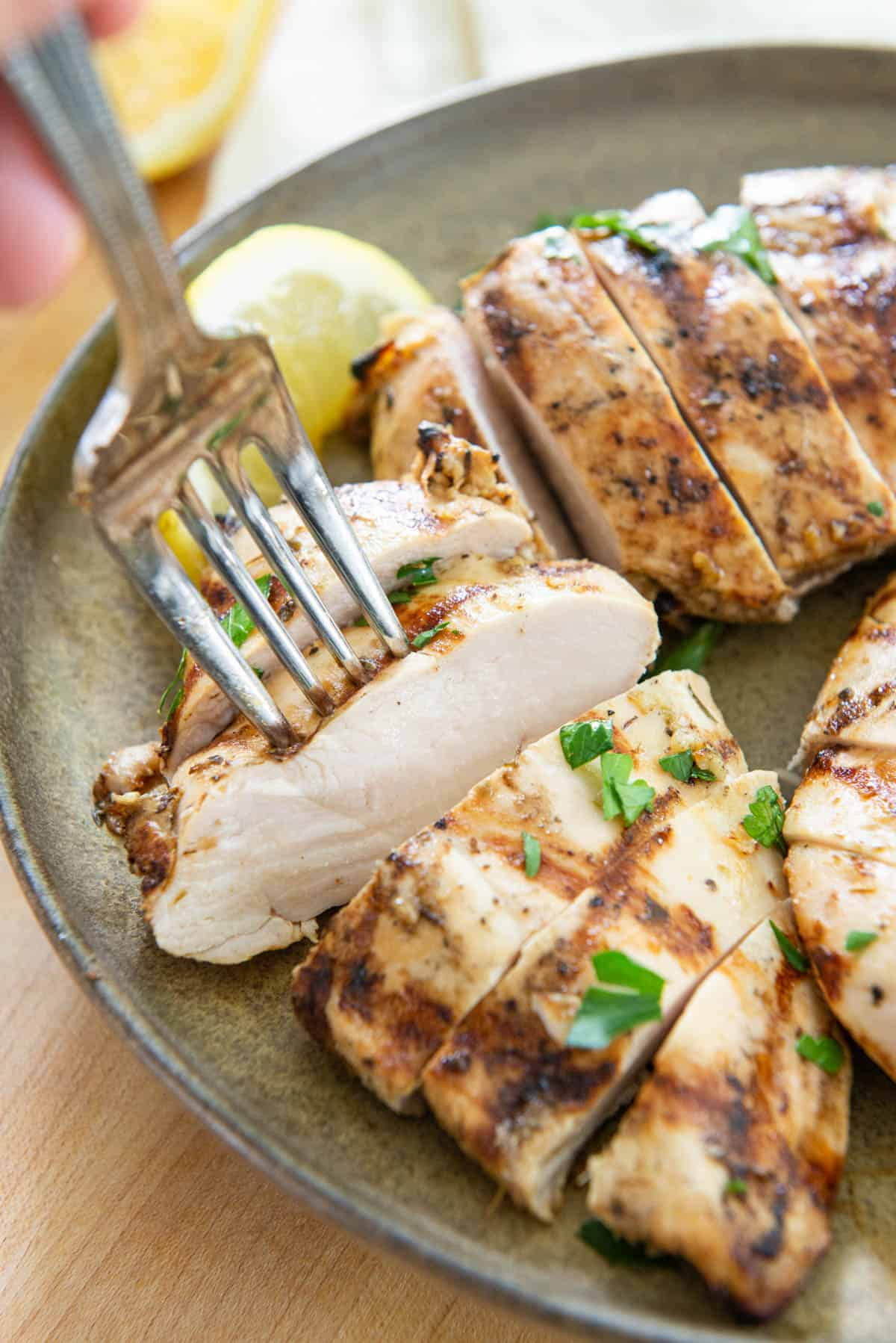 Grilled Chicken Breast Sliced On a Plate with Fork