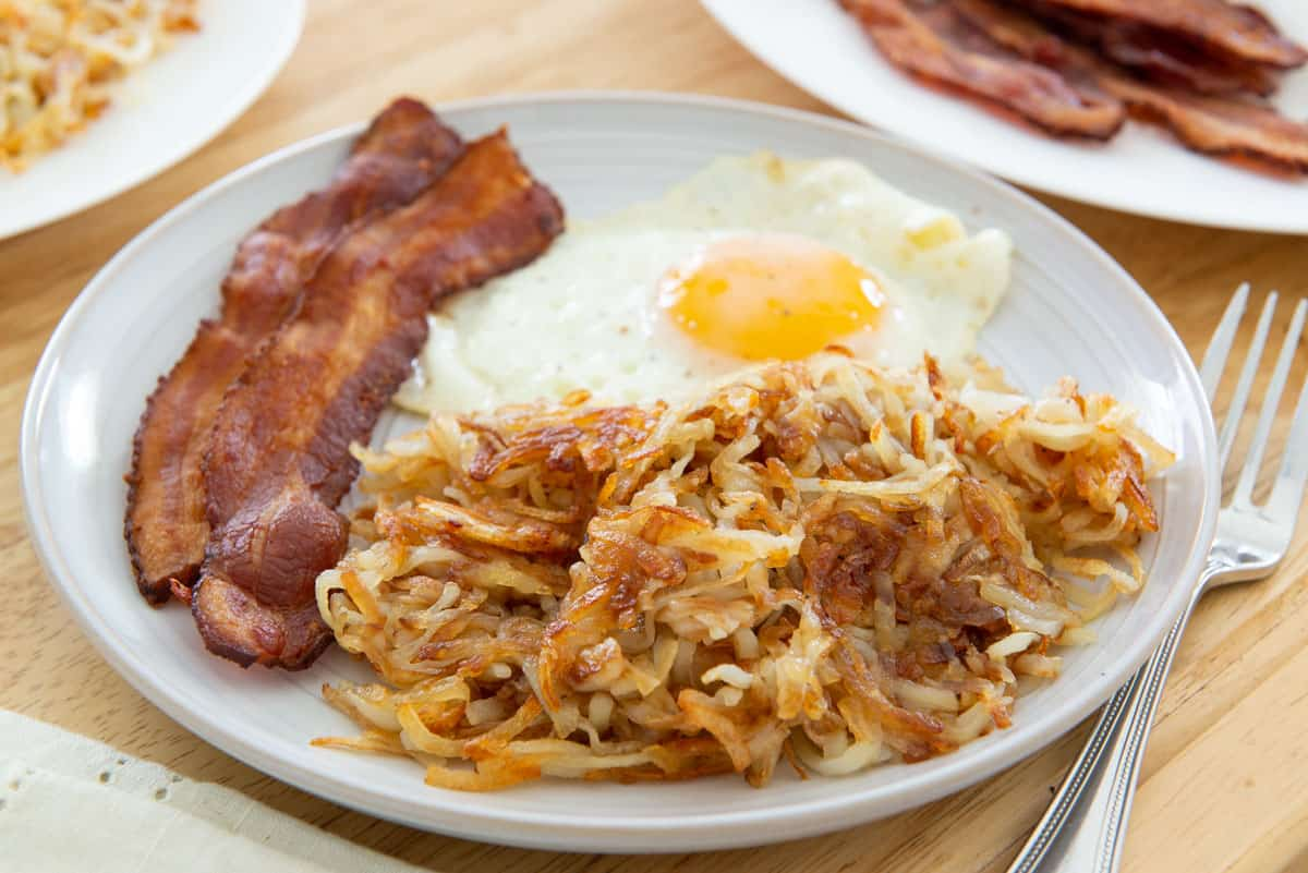 Hash Brown Recipe Plated on Gray Dish with Fried Egg and Bacon