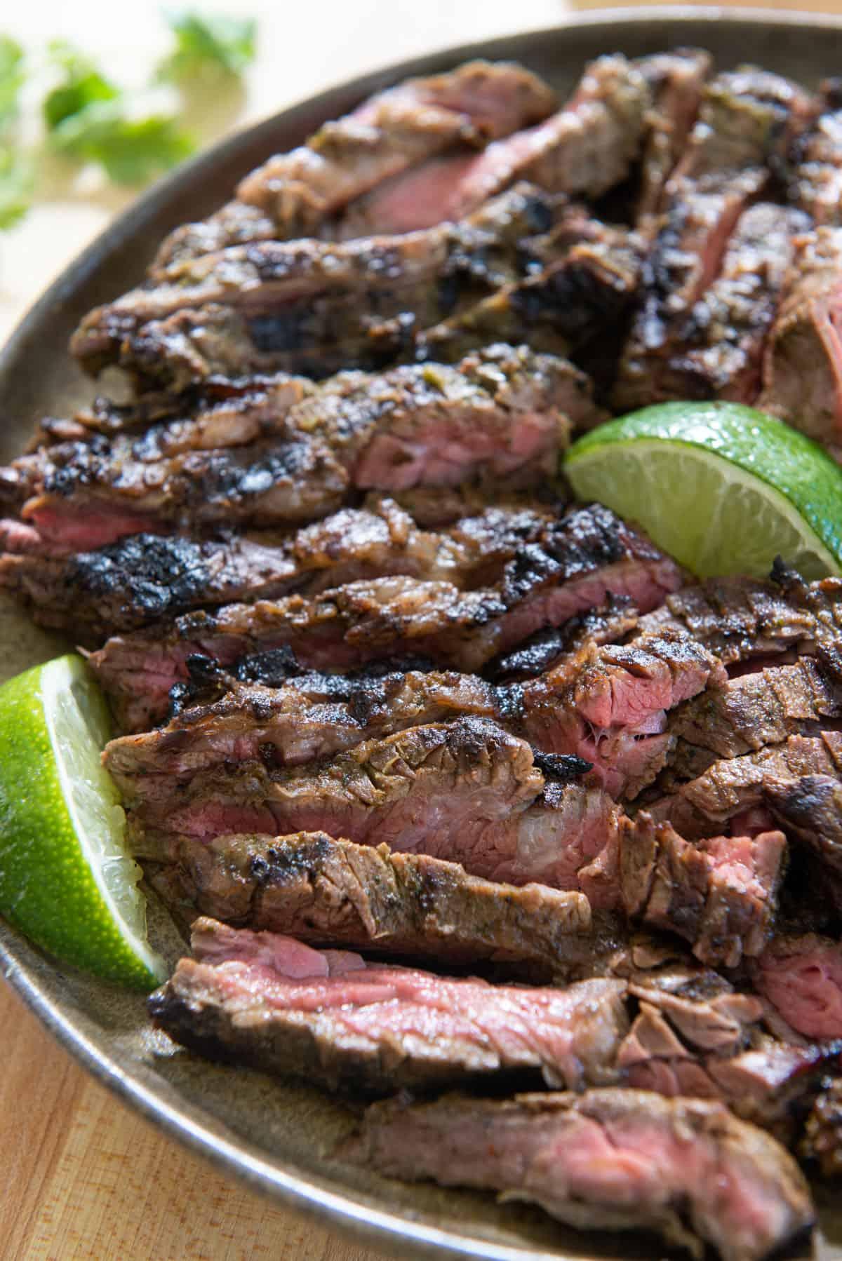 Sliced Carne Asada Skirt Steak Beef on Plate with LImes