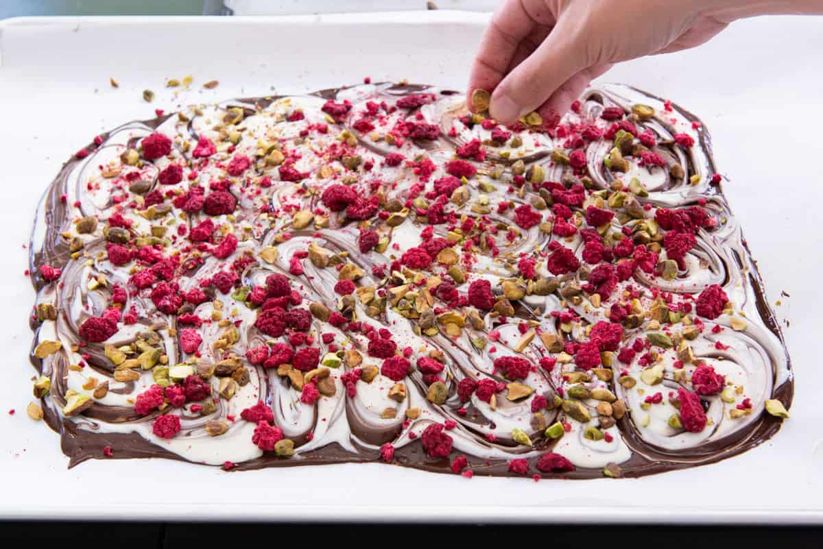 Sprinkling Chopped Pistachios and Freeze Dried Raspberries On the Slab