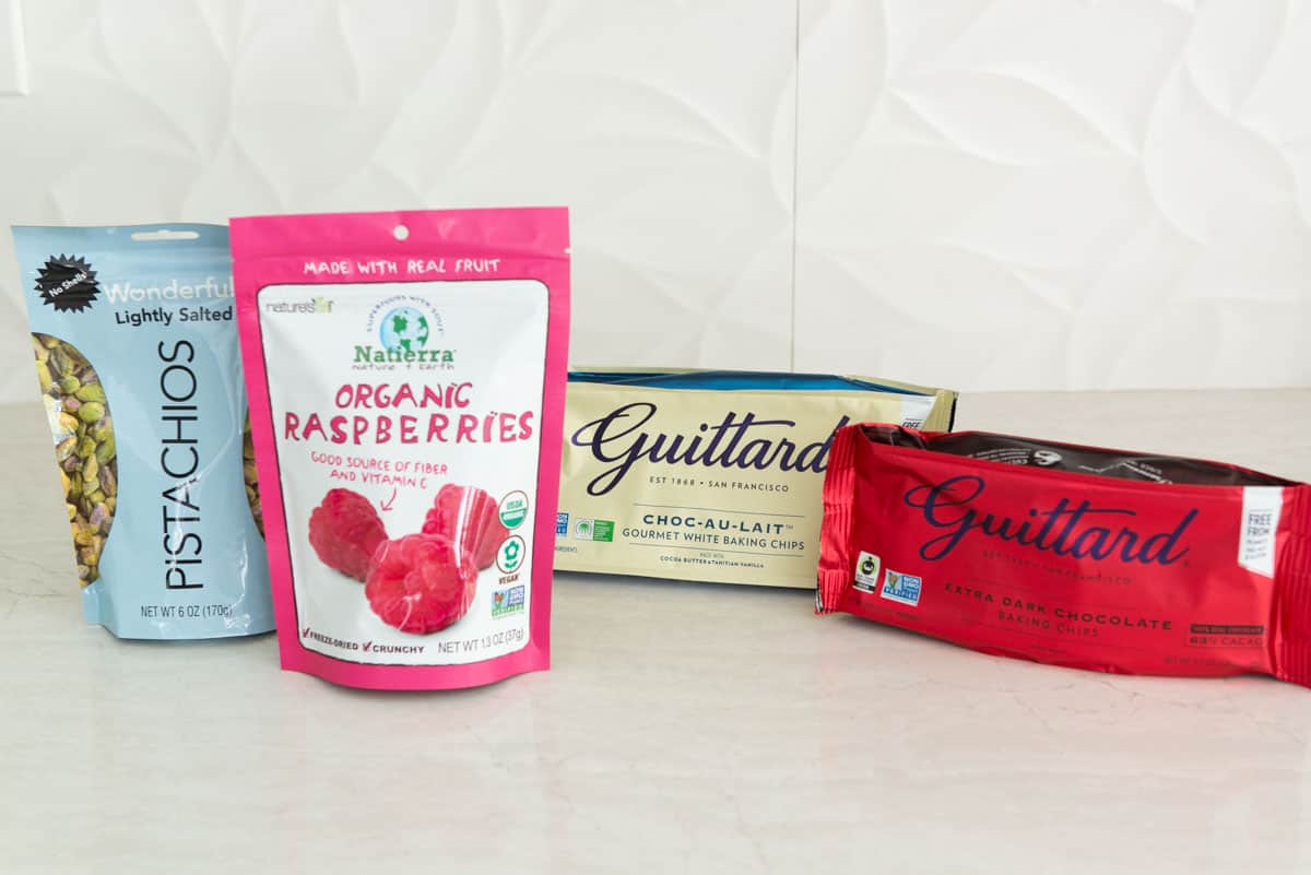 Pistachios, Raspberries, and Bags of Chocolate on Counter